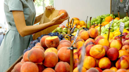 Young caucasian woman is choosing a peaches at grocery store 免版税图像