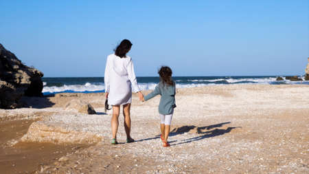 Mother with daughter is walking on the beach together.