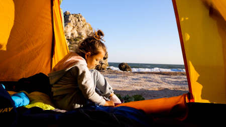 Child girl is puts her shoes while sits in camping tent at beautiful beach