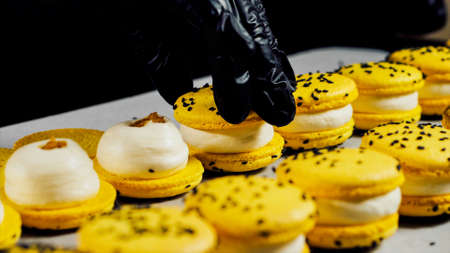Chef is assembling yellow macarons, close-up.