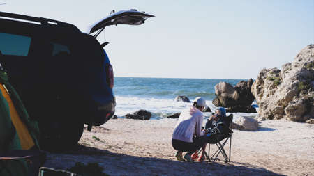Mother with daughter nearby crossover in camping at beach. 免版税图像