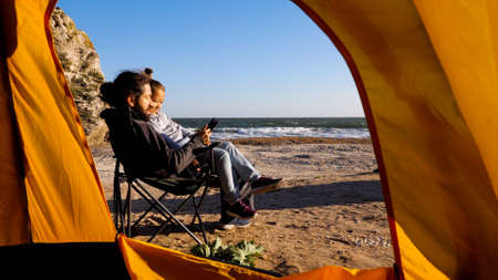 View from camping tent to father reading book little daughter on the beach