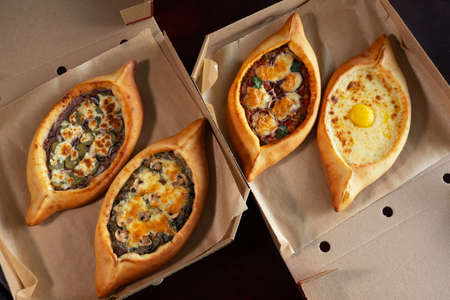 Two craft boxes with adjarian khachapuri. Food delivery concept.