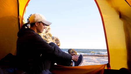 Woman is puts her shoes while sits in camping tent at beautiful beach