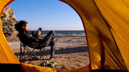 View from camping tent to bearded man is reading electronic book on the beach 免版税图像