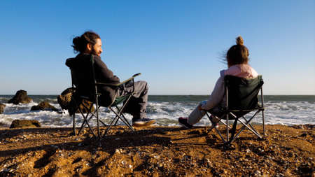 Father with little daughter sits on chairs on the beach, rear view.