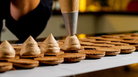 Chef is making caramel macarons, close-up.