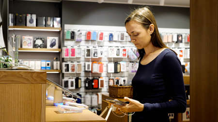 Young woman chooses a new smartphone in an electronics store.