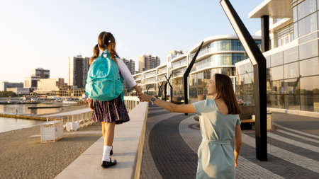 Young mother with little daughter in uniform going to school at morning