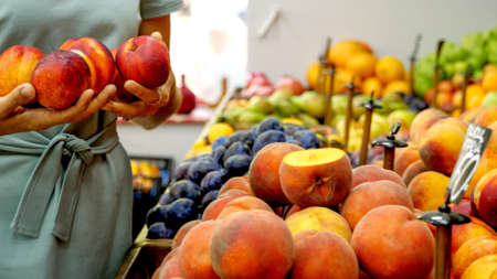 Young caucasian woman is choosing a nectarines at supermarket