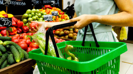 Woman with shopping basket is choosing vegetables in grocery store. 免版税图像