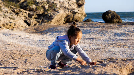 Happy little girl enjoying summer vacation and playing seashells on the beach.