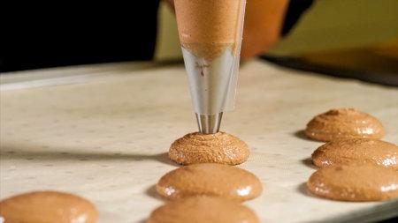 Chef making base for preparation macaron dessert.