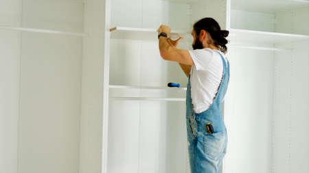 Man is installing the shelf in wardrobe 免版税图像