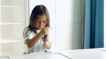 A little child girl is installing the hinges on the doors of the closet