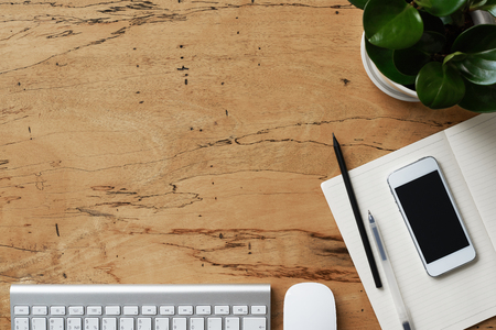 Home office stuff with keyboard, smartphone with black screen over a notebook, pencils and plant on a beautiful wooden desk. Top view, flat lay