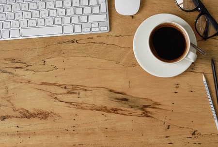 Top view of a beautiful wooden table with a keyboard, a cup of coffee