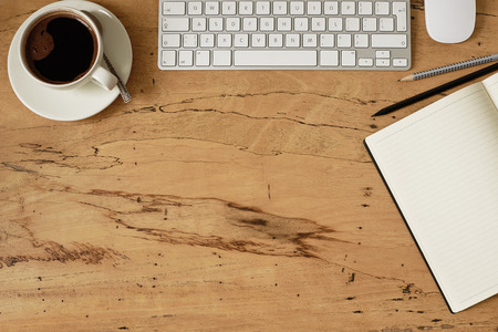 Wooden hipster desk with keyboard, mouse, cup of coffee, notebook and pen. Top view with copy space, flat lay.