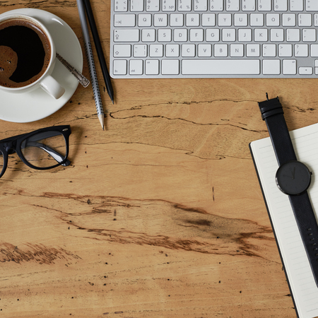 Top view of a style office working desk. Wooden table with a keyboard, a cup of coffee, eye glasses, watch and office tools with copy space, flat lay Фото со стока