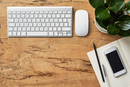 Top view on a beatiful wooden desk with keyboard, mouse, smartphone with black screen over a notebook, pencil and beautiful plant, flat lay. Designer working desk with copy space.