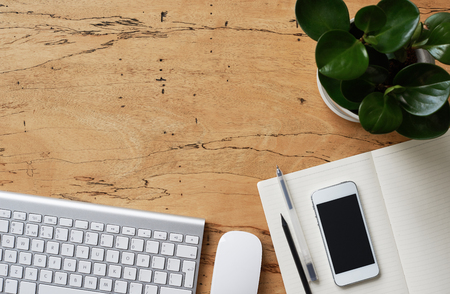 Flat lay, top view office wooden desk. Workspace with keyboard, diary, office tools, smartphone with black screen and indoor plant
