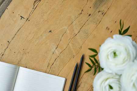 Top view of blank notepad, black pencils and bouquet of white flowers ranunculus on a solid wooden desk. Empty space for your promotional product or text. Overhead view, flat lay