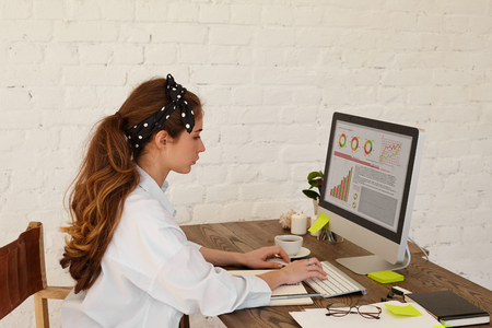 Attractive young financial consultant female dressed in light blue shirt analyzing financial chart working in the office IT company. The young specialist female prepares for a meeting with director