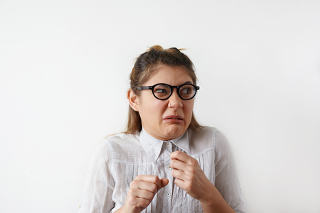 Headshot of disgusted Caucasian student girl in shirt and glasses looking aside with fearfyl and suspicions, holding her fist up.Comic portrait of woman having negative emotions and facial expressions