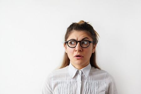 Human face expressions and emotions. Portrait of young desperate woman in striped shirt looking panic, mouth wide open. Female student in despair and shock looking aside with fear on her face Фото со стока