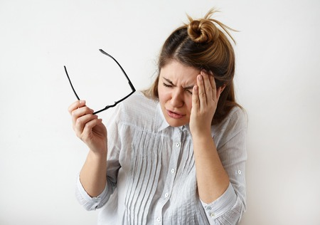 Closeup portrait of young upset woman suffering from stress thinking about something with headache holding her hands on head isolated on gray wall background. Negative human facial expression