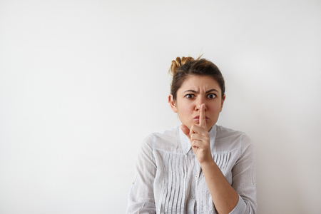 Portrait of funny young Caucasian woman in white shirt with hair bun looking seriously at the camera, holding index finger at lips, asking to keep silence or not tell anyone her secret, saying Tsss