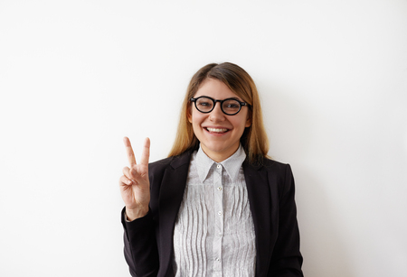 Headshot of a cheerful happy female student in formal outfit showing victory sign and looking at camera isolated on the white background. Pretty girl looking at the camera posing with peace gesture Фото со стока