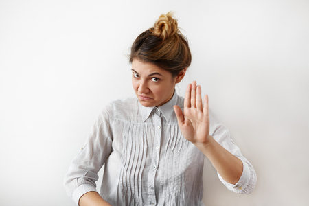 Portrait of young woman making stop gesture with her hand. Young woman with funny facial expressions refuses junk food, to discuss gossip showing her hand stop sign. Expressive facial expressions