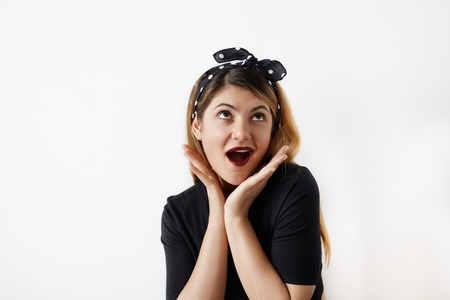 Portrait of beautiful young surprised woman, dressed in pin-up style holds cheeks by hand and looks up. Caucasian blond model screaming Wow posing in vintage concept. Expressive facial expressions Фото со стока