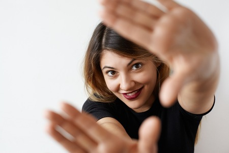 Close up portrait of pretty student female with cute smile looking at camera with happy joyful expression and gesturing hands frame on white background. Selective focus on face. Having fun concept Фото со стока