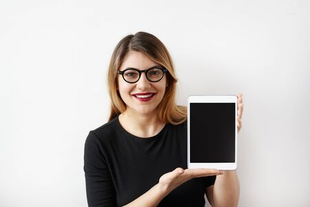 Stylish young Caucasian female in black dress and glasses looking at camera and laughing cheerfully, holding her digital tablet showing to blank tablet pc monitor. Copy space for your content
