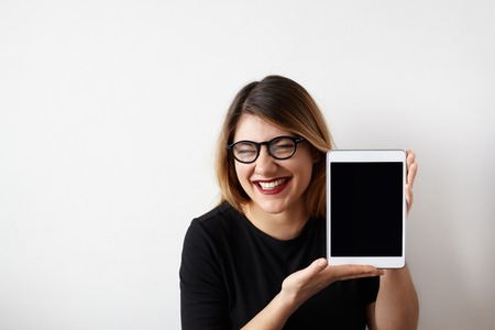 sarcastic: Humorous portrait of attractive young woman in glasses showing blank copy screen tablet, having funny sarcastic face expression, loud laughing meaning gloating, talking muahaha. Copy space for text