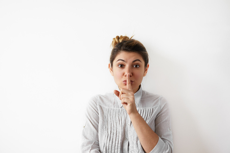 Keep silence! Portrait of pretty young businesswoman wearing in white striped shirt holding her finger near lips and making silence gesture asking to keep confidential information private Фото со стока