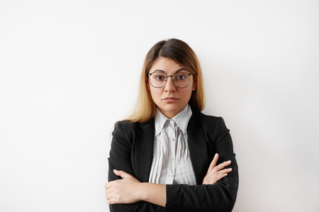 Portrait of successful young entrepreneur female in black suit and shirt wearing glasses looking confident and serious. Thoughtful young businesswoman standing staring at camera with folded arms Фото со стока