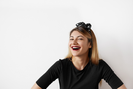 Funny woman on white background. Portrait of woman smiling with perfect smile and white teeth looking laugh loudly. Cheerful female model joyful. Positive human emotion facial expression body language