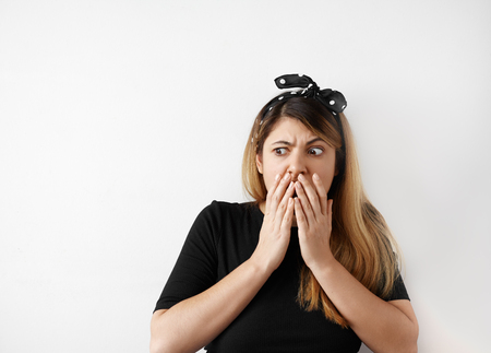 Portrait of shocked scared young woman in casual black dress and headscarf, hearing bad news with disgusting emotion on her face, feeling scare, screaming Omg. Human face expressions, body language