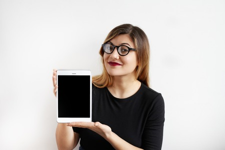 Attractive young businesswoman with pretty smile wearing black dress ang eyeglasses looking at camera and showing a digital tablet computer with blank copy screen for your advertising content.