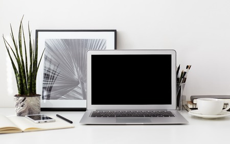 Creative designer desktop with blank copy screen laptop, bw photo in a frame, smartphone, stationery, green plant in a pot, cup of coffee on white wall background. Stylish hipster workspace, mock up Фото со стока