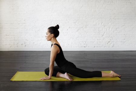 Urdhva mukha svanasana. Asian female in sport clothes performing exercise yoga early morning in a modern training yoga hall background. Yoga and health concept. Copy space for advertising content