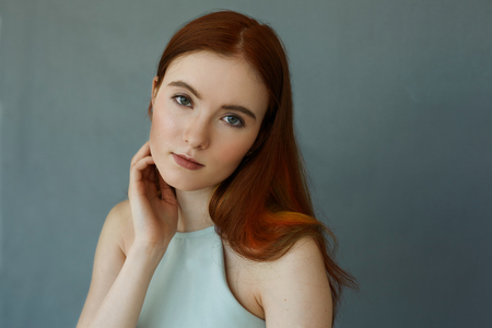 Indoor portrait of cute redhead girl with beautiful green eyes looking at camera with pensive and serious face expression. Cropped shot of charming ginger female model on Cadet blue wall background Фото со стока