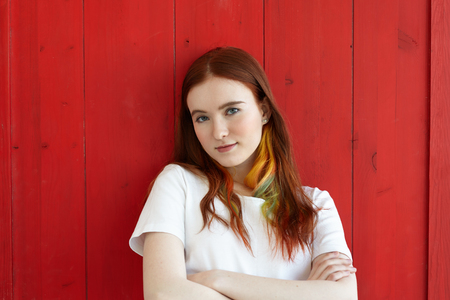 Handsome girl with colored strands in ginger long hair wearing white top looking at camera with folded arms. Half body shot of green-eyed student female with crossed arms Фото со стока