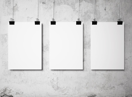three blank poster hanging on a white background painted walls Archivio Fotografico