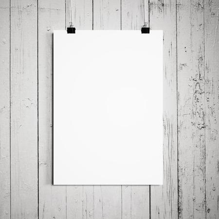 木製の壁の白い背景に掛かっている空白のポスター