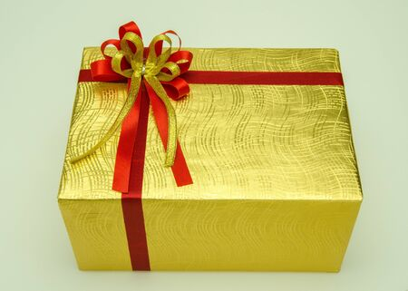 Golden gift box with red bow tie with yellow trim.