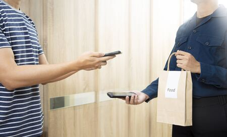 Man recieve food in paper bag delivery using smartphone scan payment digital wallet.